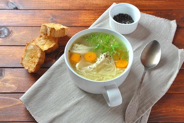 Hühnersuppe mit nudeln und gemüse in der schüssel auf holzoberfläche hausgemachte gesunde mahlzeit