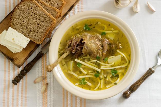 Hühnersuppe zama traditionelle moldauische oder rumänische suppe serviert mit käse, brot und knoblauch. rustikaler stil.