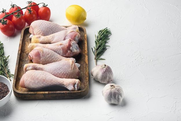 Hühnertrommelstock mit gewürzen und kräutern auf weißem tisch