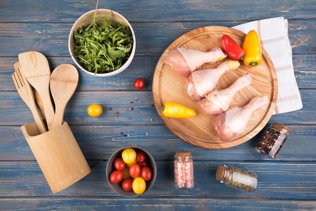 Hühnertrommelstöcke der flachen lage auf hölzernem brett mit pfeffern und tomaten