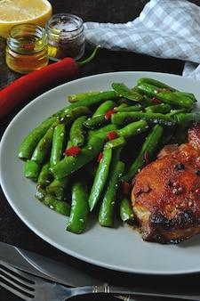 Hülsen der grünen erbse und schweinefleischsteak auf einer platte. keto-diät.