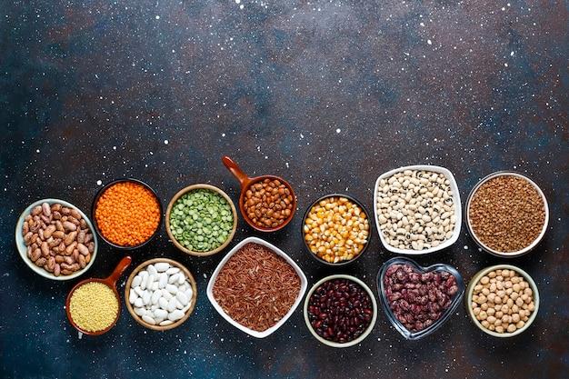 Hülsenfrucht- und bohnensortiment in verschiedenen schalen auf hellem steinhintergrund. draufsicht. gesunde vegane eiweißnahrung.