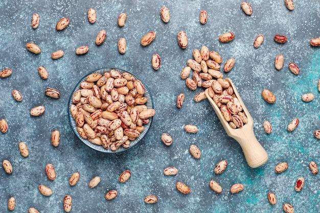 Hülsenfrucht- und bohnenzusammenstellung in den verschiedenen schüsseln auf heller steinoberfläche. ansicht von oben. gesunde vegane proteinnahrung.