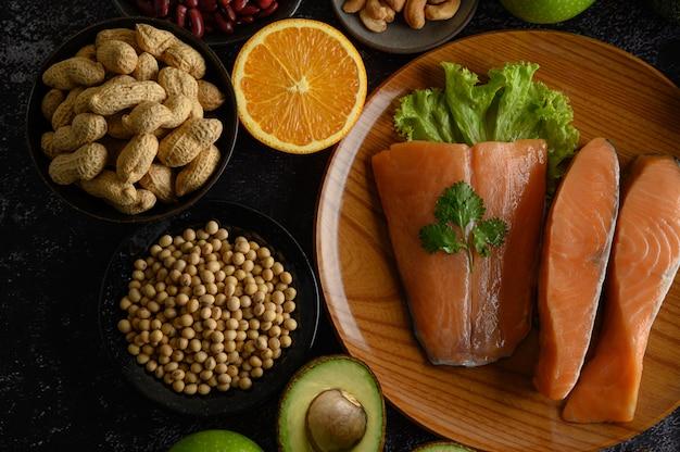 Hülsenfrüchte-, frucht- und lachsstücke auf einer hölzernen platte.
