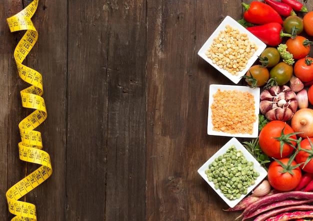 Hülsenfrüchte in schalen und rohem gemüse mit maßband auf holztischoberansicht mit kopierraum