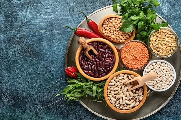 Hülsenfrüchte, linsen, kichererbsen, bohnensortiment, leckere, appetitliche zutaten, gewürze lebensmittelgeschäft zum kochen gesunder küche auf schwarzem tisch. gewichtsverlustdiät und kampf gegen das cholesterinkonzept. ansicht von oben.