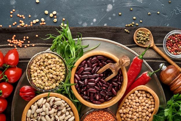 Hülsenfrüchte, linsen, kichererbsen, bohnensortiment, leckere, appetitliche zutaten, gewürze lebensmittelgeschäft zum kochen gesunder küche auf schwarzem tisch