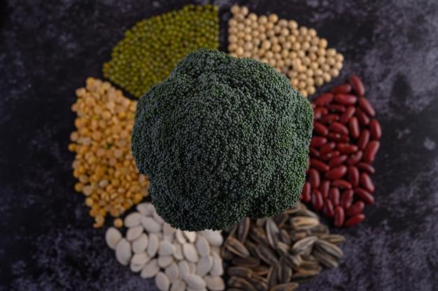 Hülsenfrüchte mit brokkoli auf einer schwarzen zementbodenoberfläche.