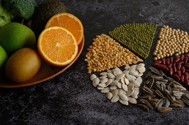 Hülsenfrüchte mit orange beinahe eingeschnitten, kivi und apfel auf schwarzem zementboden.