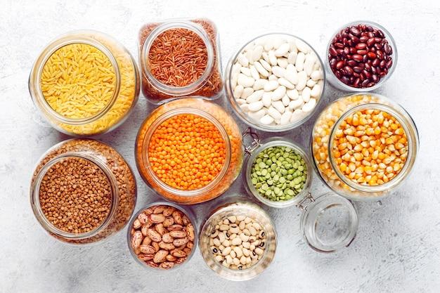 Hülsenfrüchte und bohnensortiment in verschiedenen schalen auf hellem stein. draufsicht. gesunde vegane eiweißnahrung.