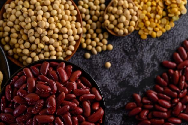 Hülsenfrüchte und bohnenzusammenstellung auf dem schwarzen zementboden.