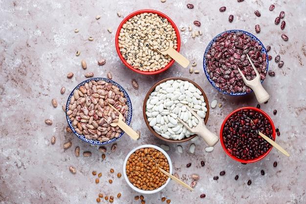 Hülsenfrüchte- und bohnenzusammenstellung in den verschiedenen schüsseln auf hellem steinhintergrund. ansicht von oben. gesunde vegane proteinnahrung.