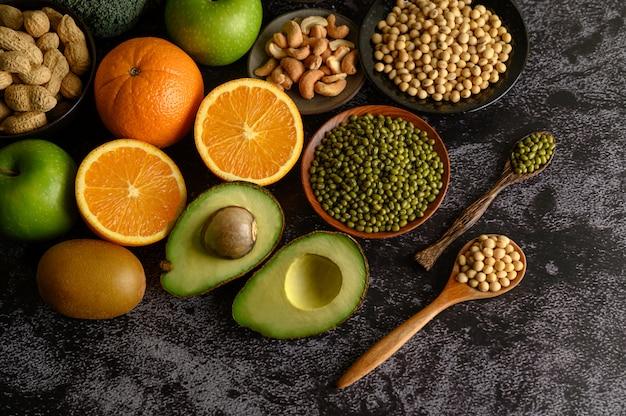 Hülsenfrüchte und frucht auf einer schwarzen zementbodenoberfläche.