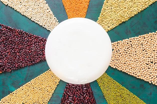 Hülsenfrüchte und getreide sind wie sonnenstrahlen auf smaragdgrünem hintergrund mit runder platte in der mitte ausgelegt.