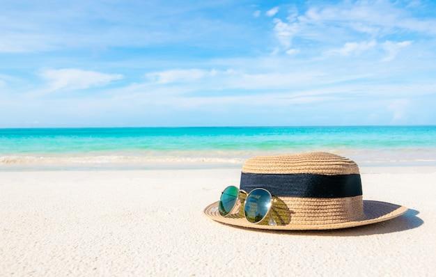 Hüte und gläser am strand und am meer sorgen für einen erholsamen sommerurlaub