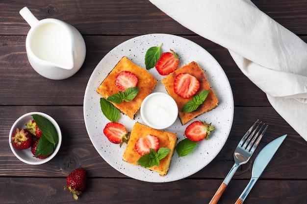 Hüttenkäse-auflauf mit erdbeeren und minze. köstliches hausgemachtes dessert aus quark und frischen beeren mit sahne. dunkler hölzerner hintergrund, kopienraum.
