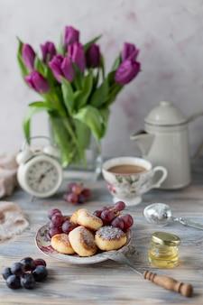 Hüttenkäse-dessert, käsekuchen auf dem tisch mit einem strauß tulpen, uhren und obst auf einem holztisch am fenster.
