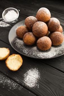 Hüttenkäse donuts auf dem schwarzen teller auf der dunklen holzoberfläche