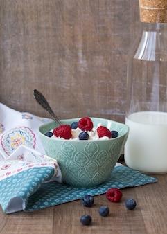 Hüttenkäse in der blauen schüssel mit himbeeren und blaubeeren und milch auf hölzernem hintergrund. gesundes frühstück