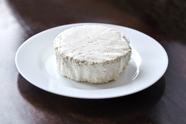 Hüttenkäse in der weißen keramikplatte auf dem dunklen holztisch. quark - milchprodukt