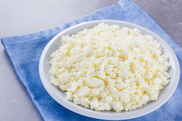 Hüttenkäse in einer platte. frischer hüttenkäse in der weißen platte. weichkäse auf einer blauen serviette