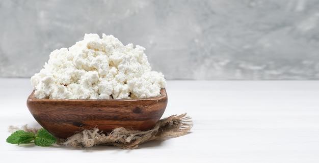 Hüttenkäse in einer traditionellen holzschale auf weißem hintergrund aus holz. nahaufnahme, selektiver fokus mit kopienraum. weicher quark natürliches gesundes essen, vollwertige diätnahrung