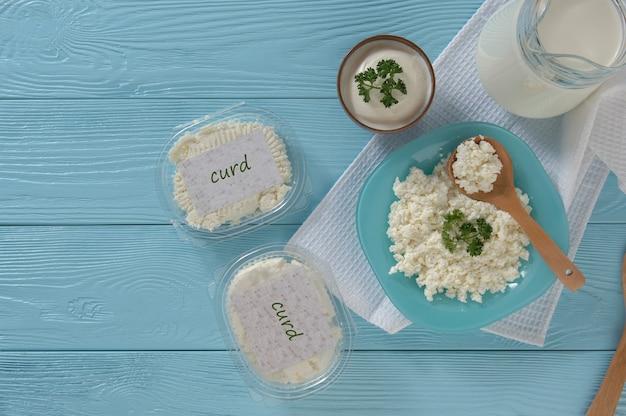 Hüttenkäse in plastikverpackungen und milch auf einem hölzernen blauen hintergrund konzept der gesunden ernährung