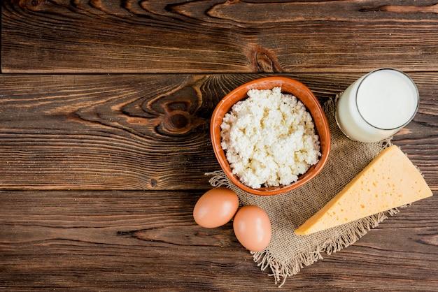 Hüttenkäse, käse und glas milch auf hölzernem hintergrund. milchprodukte.
