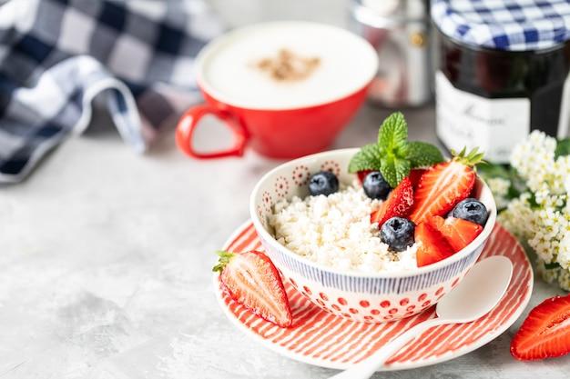 Hüttenkäse mit beeren, marmelade, frischen erdbeeren und einer tasse kaffee mit sahne zum frühstück.
