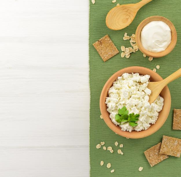 Hüttenkäse mit sauerrahm in einer holzschüssel und einem löffel auf einem weißen holztisch. gesunde milchprodukte. platz kopieren