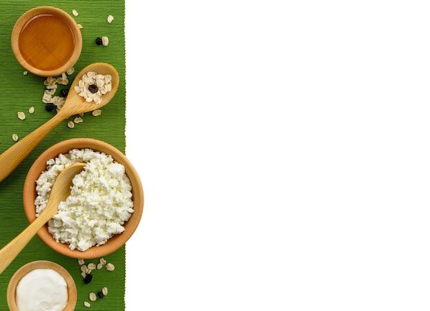 Hüttenkäse mit sauerrahm und honig in einer holzschale und einem löffel auf weißem hintergrund. gesunde milchprodukte auf grünem stoffrand. platz kopieren