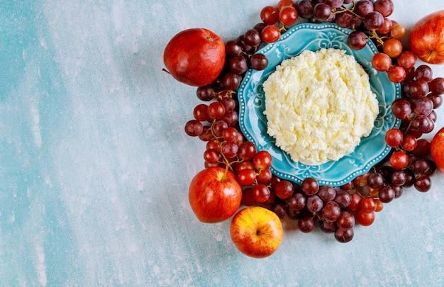 Hüttenkäse mit trauben und äpfeln auf blauer oberfläche