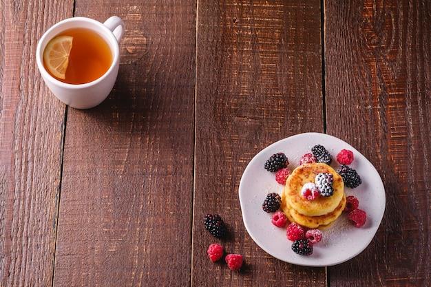 Hüttenkäse-pfannkuchen, quark-krapfen-dessert mit himbeer- und brombeer-beeren in der platte nahe heißer teetasse mit zitronenscheibe auf dunkelbraunem holztisch, winkelansicht-kopienraum