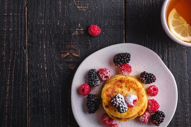Hüttenkäse-pfannkuchen, quark-krapfen-dessert mit himbeer- und brombeer-beeren in platte nahe heißer teetasse mit zitronenscheibe auf dunkelschwarzem holztisch, draufsicht-kopienraum