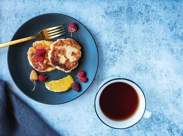 Hüttenkäse pfannkuchen russische syrniki auf einem schwarzen teller mit beeren orange und tasse tee mit kopie platz