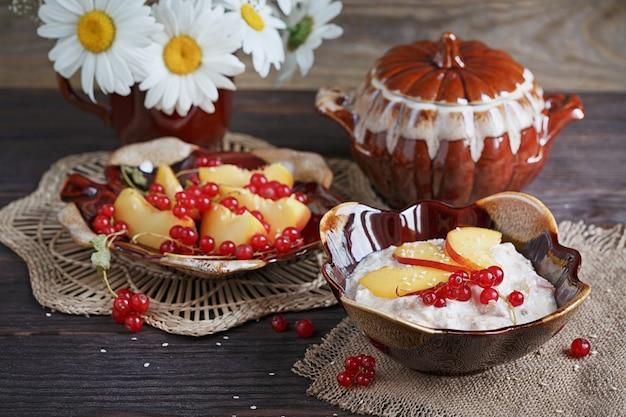 Hüttenkäse, rote johannisbeere und frische pfirsiche auf holzoberfläche