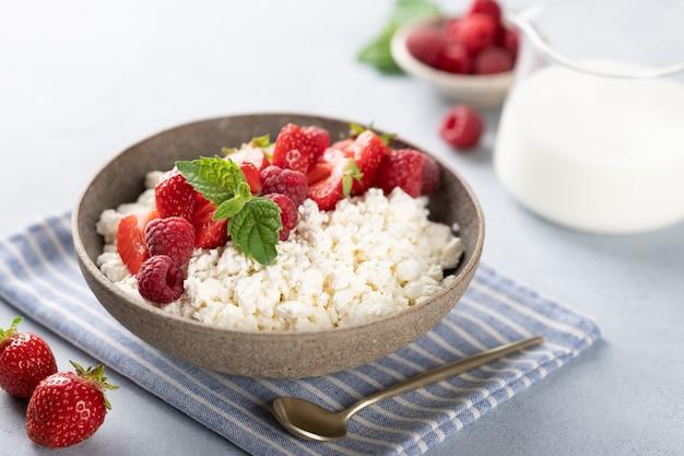 Hüttenkäse schüssel mit himbeeren und erdbeeren auf einem weißen hintergrund