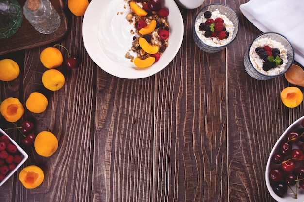 Hüttenkäse und joghurt mit beeren und fruchtaprikose für ein gesundes frühstück. ansicht von oben. platz kopieren.
