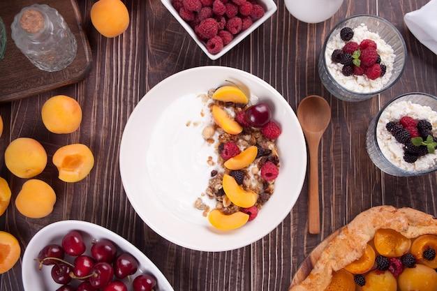 Hüttenkäse und joghurt mit gronala, beeren und fruchtaprikose für ein gesundes frühstück. ansicht von oben.