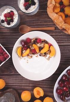 Hüttenkäse und joghurt mit müsli, beeren und aprikosenfrüchten für ein gesundes frühstück.