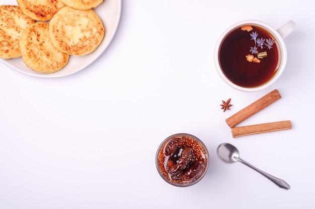 Hüttenkäsekrapfen mit feigenmarmelade und heißem schwarzen aromatischen tee, weihnachtsfrühstücksstimmung mit anis und zimt auf weißer oberfläche, draufsicht