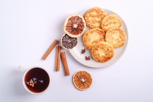 Hüttenkäsekrapfen mit heißem schwarzem aromatischem tee, weihnachtsfrühstücksstimmung mit anis und zimt auf weißem hintergrund, draufsicht