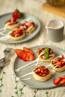 Hüttenkäsekuchen mit erdbeeren und sauerrahm auf tellern frühstückstisch hochwertige fotoansicht von oben