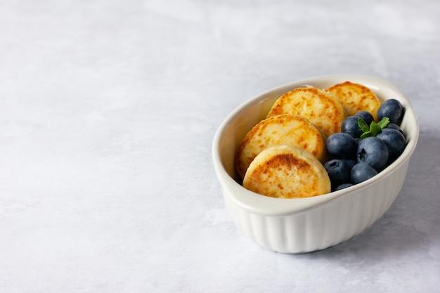 Hüttenkäsepfannkuchen auf einem hellen hintergrund. syrniki mit frischen blaubeeren. pfannkuchen mit hüttenkäse auf einem weißen teller. kopieren sie platz für ihren text.
