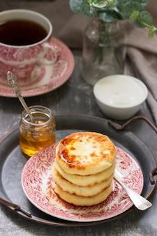 Hüttenkäsepfannkuchen, hausgemachtes syrniki mit honig und sauerrahm.