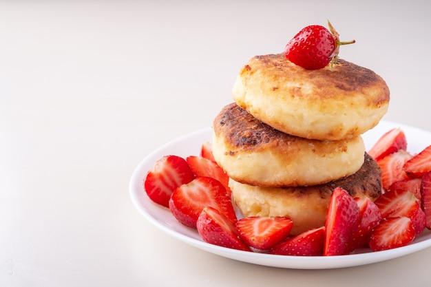 Hüttenkäsepfannkuchen mit einer erdbeere auf weißer platte isolierte winkelansicht