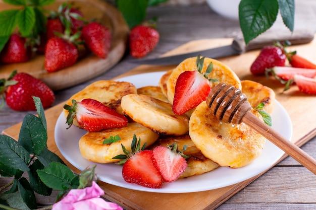 Hüttenkäsepfannkuchen mit erdbeere auf einem weißen teller auf einem holztisch. frühstücks- oder mittagskonzept.