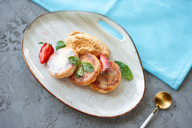 Hüttenkäsepfannkuchen mit erdbeere und zuckerpulver