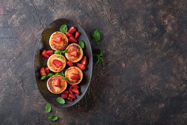 Hüttenkäsepfannkuchen mit erdbeeren und minze auf einem draufsichtfoto der schwarzen platte mit freiem speicherplatz