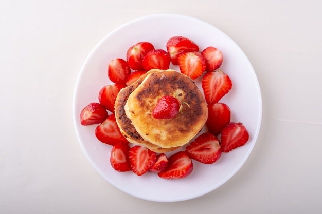 Hüttenkäsepfannkuchen mit geschnittenen erdbeeren auf weißem teller isoliert